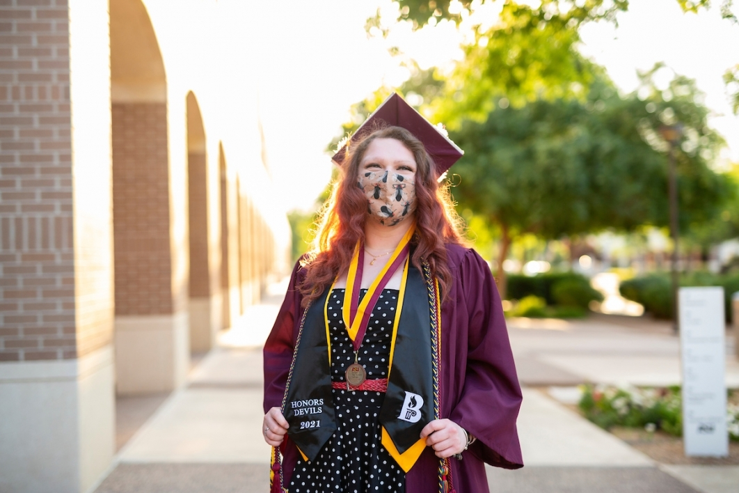 woman wearing a mask and a cap and gown standing outside of a building