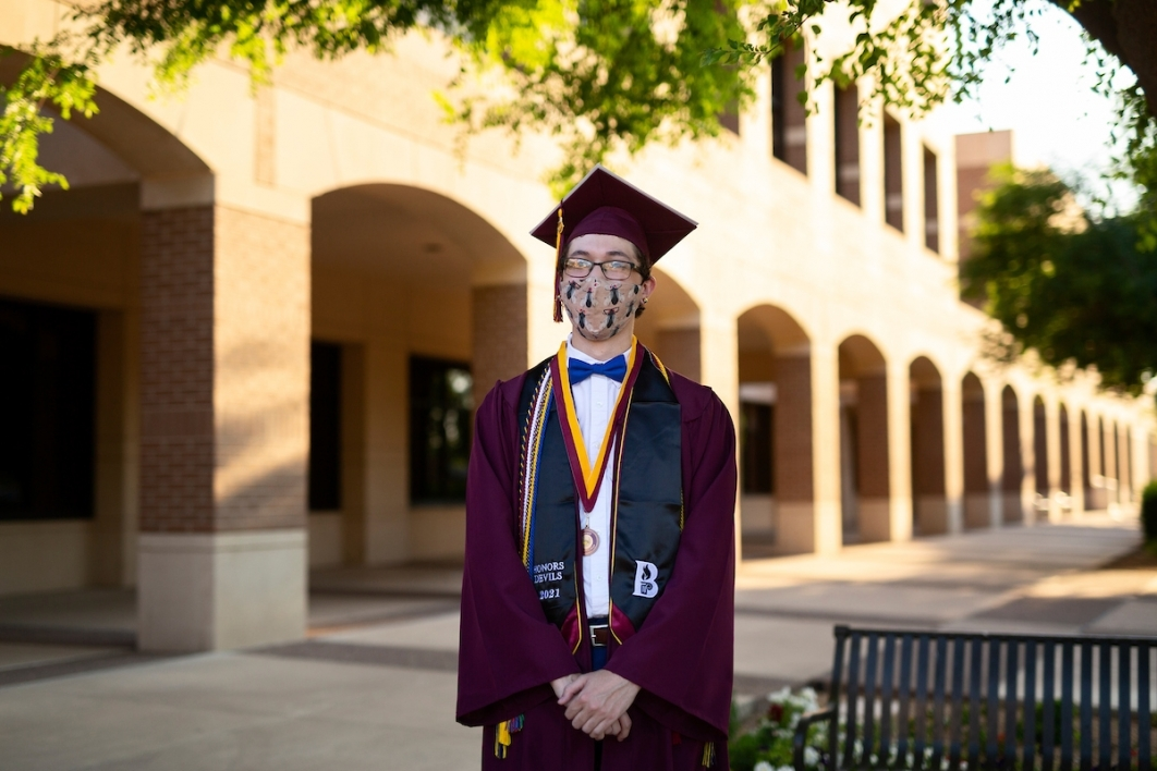 man wearing a mask and a cap and gown standing outside of a building