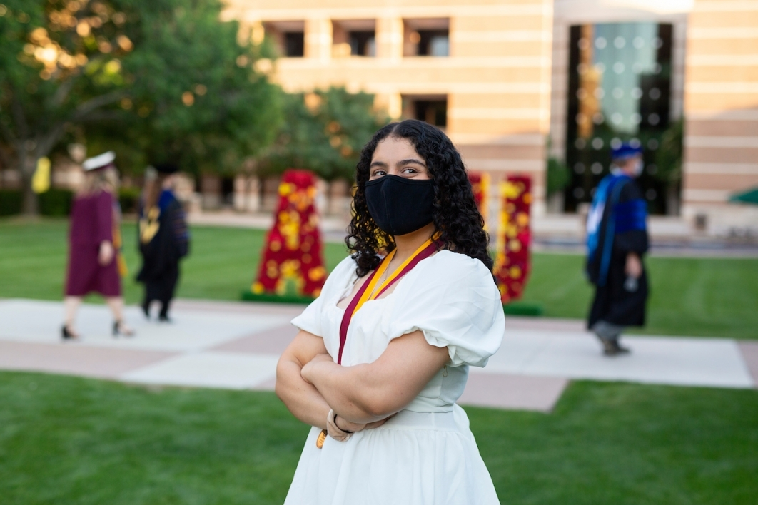 woman in a mask and white dress poses on ASU West campus' Fletcher Lawn