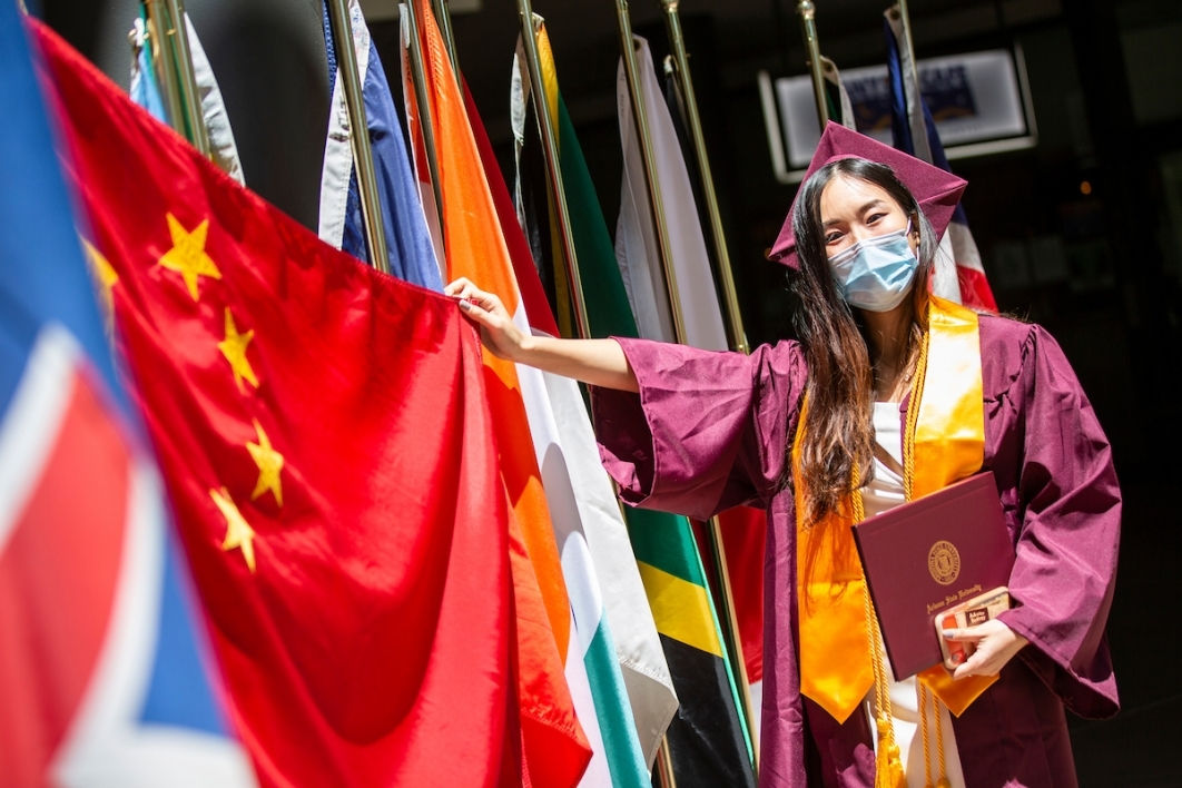Xi Ling holds up her country's flag at Thunderbird ceremony