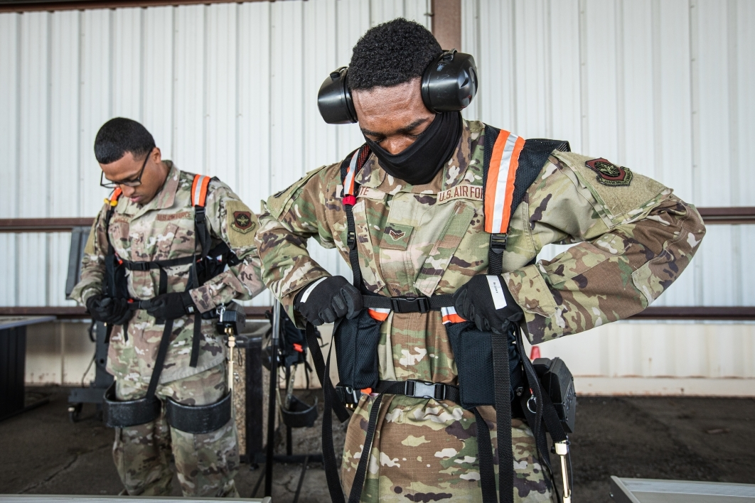 Two men in military camo attach an exoskeleton vest frame over their uniforms