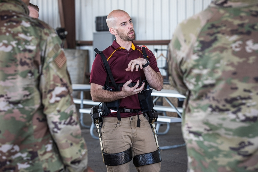 A man not in uniform demonstrates an exoskeleton to a group in military camo