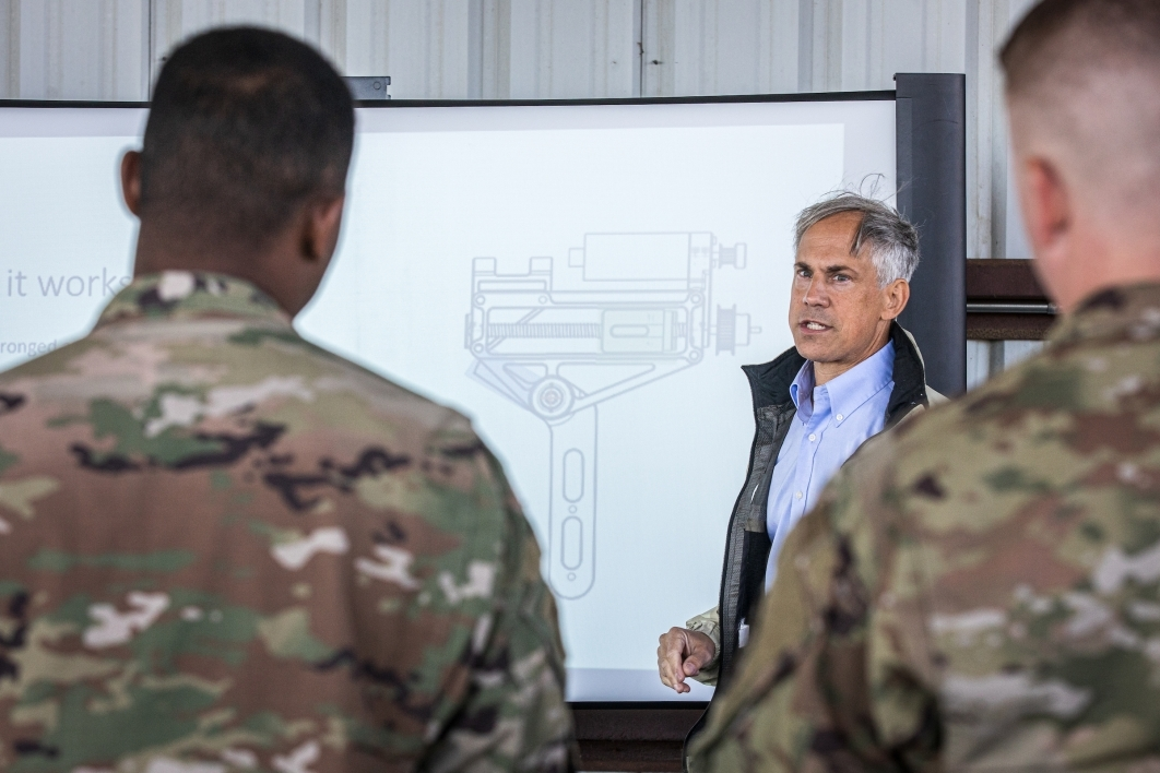 A man not in uniform explains a diagram on a board to a group of military members