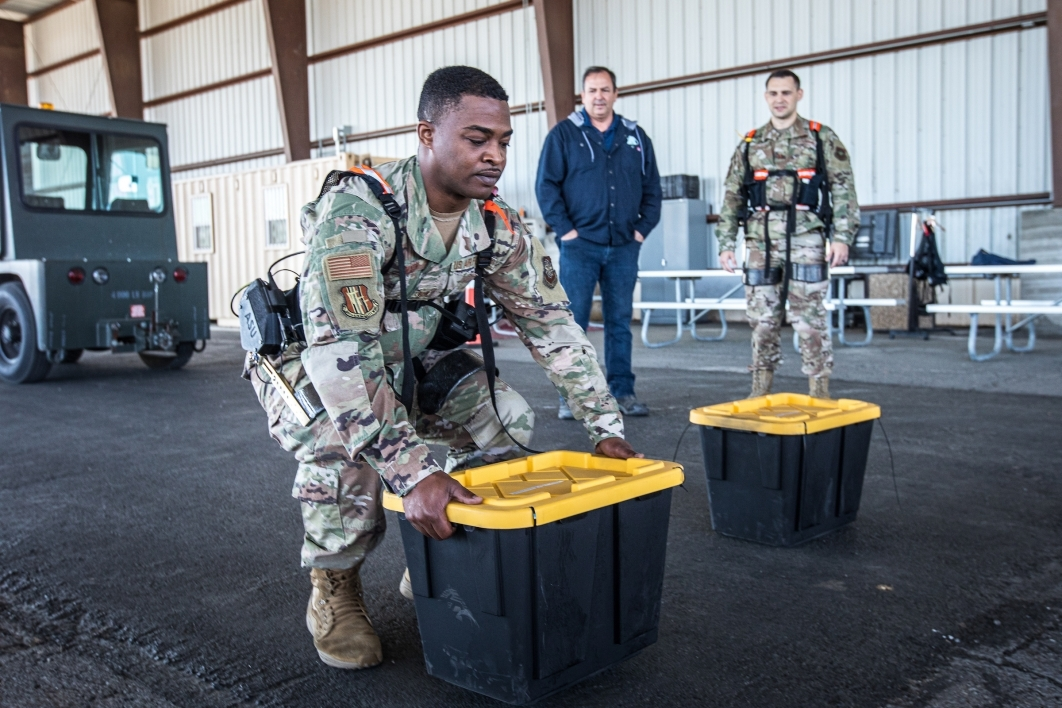 A man in military camo lifts a 50-pound tub while wearing an exoskeleton vest