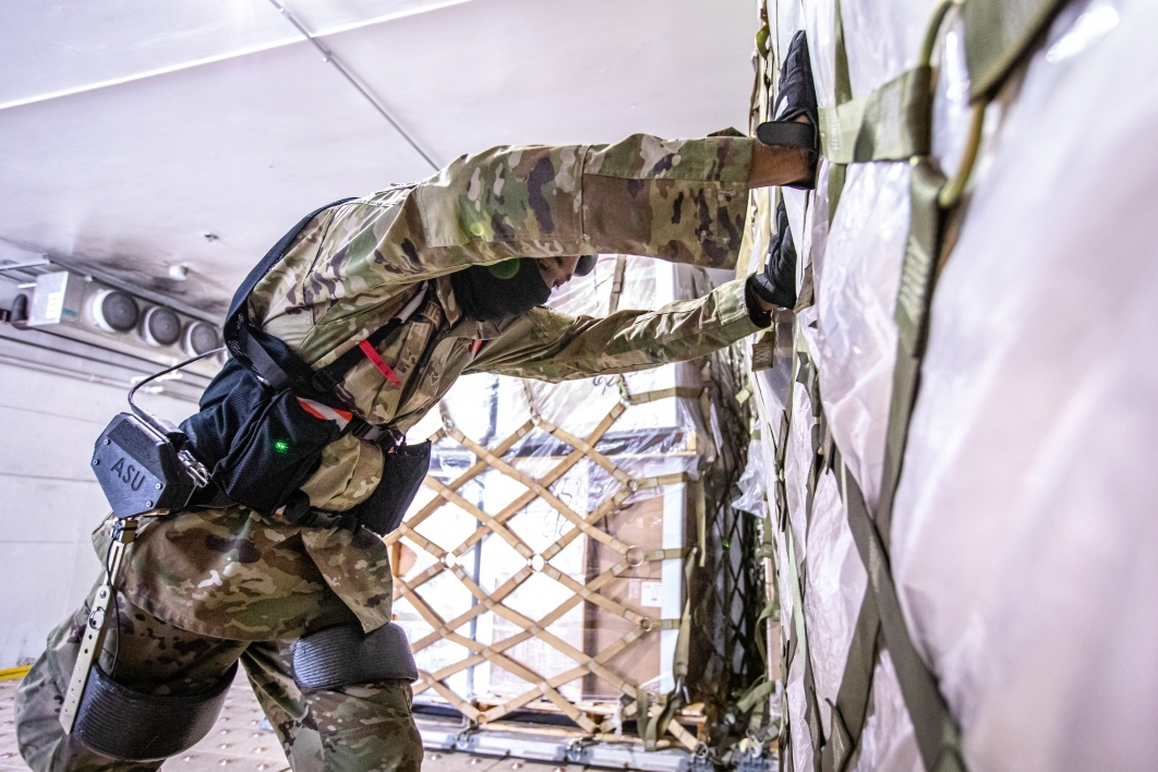 A man wearing military camo and an exoskeleton pushed a loaded-down pallet of supplies