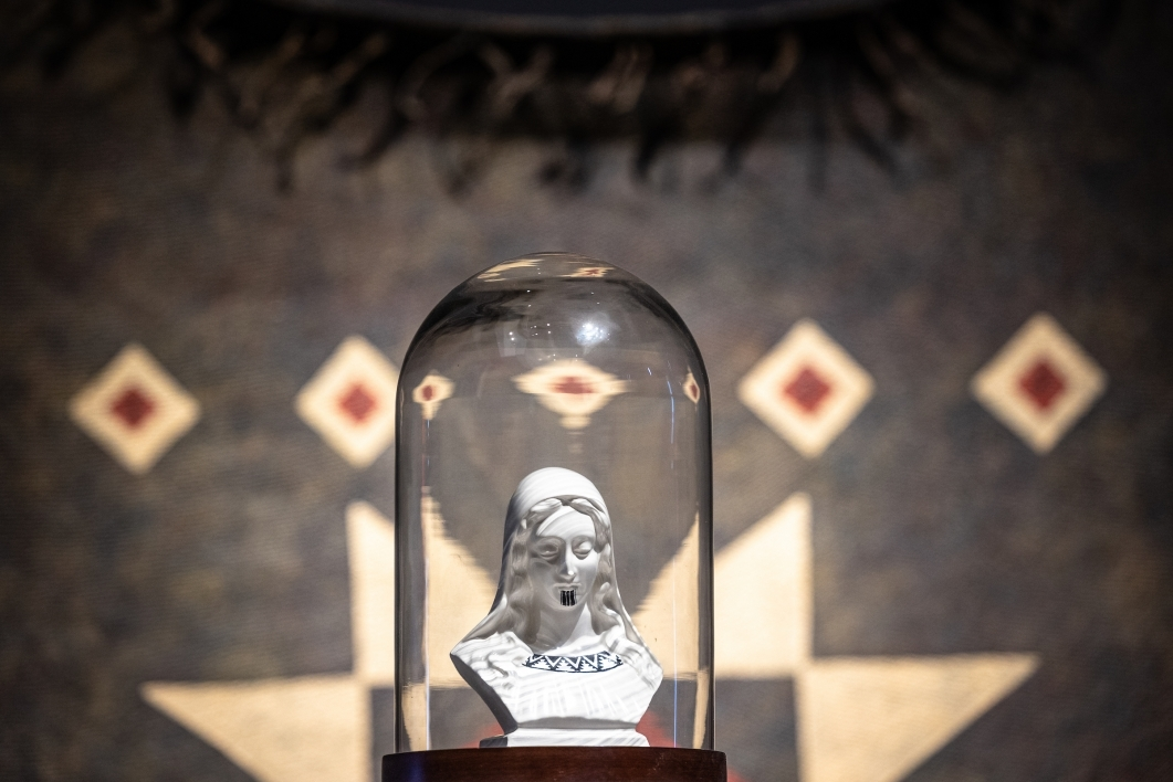 A religious icon from a thrift store sits under a glass dome