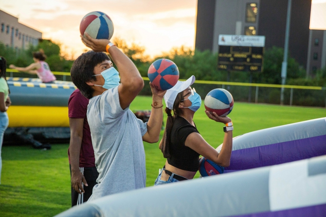 Masked students playing a basketball carnival game