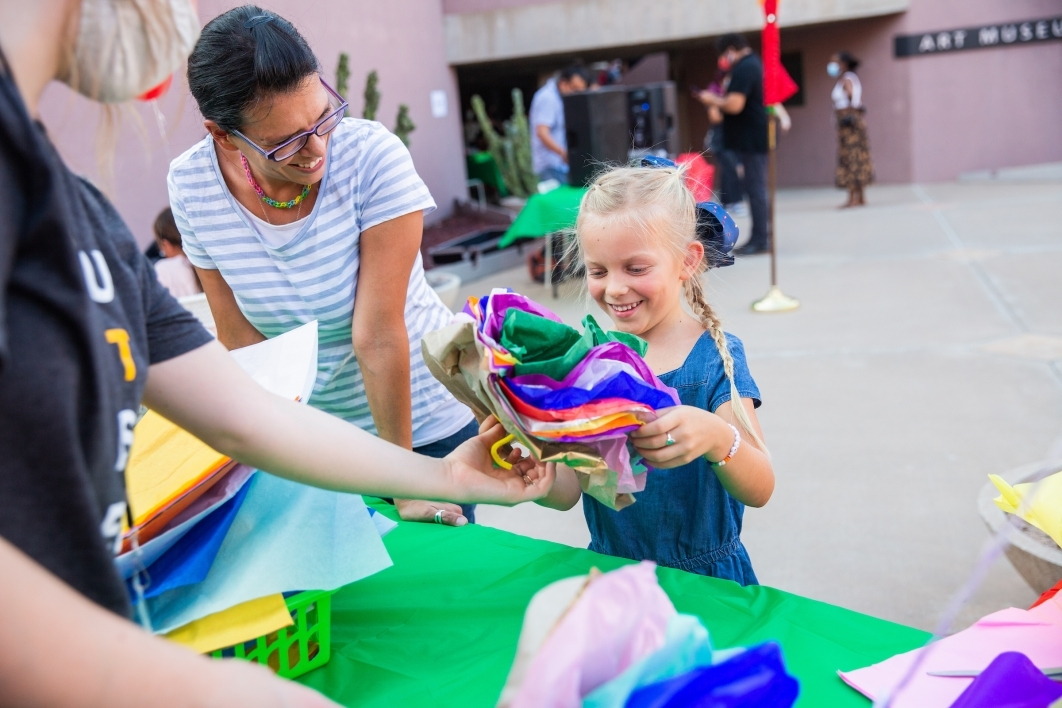 A little girl holds a stack of tissue paper at a craft table as her mom looks on and smiles
