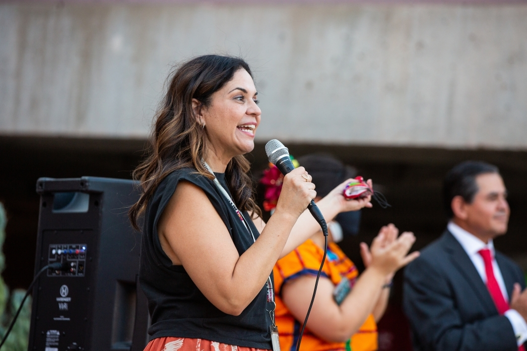 A woman speaks at a microphone