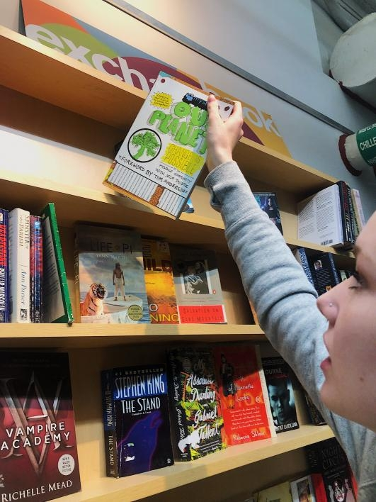 student takes a book off a shelf