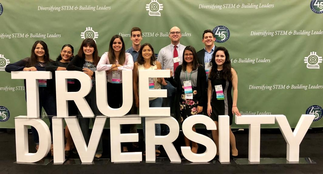 "group photo in front of a sign reading ""True Diversity"""