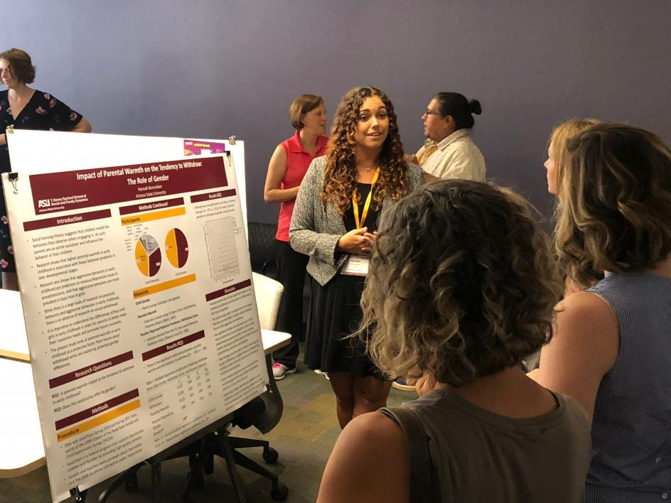 Super fellow presenting her research poster to faculty.