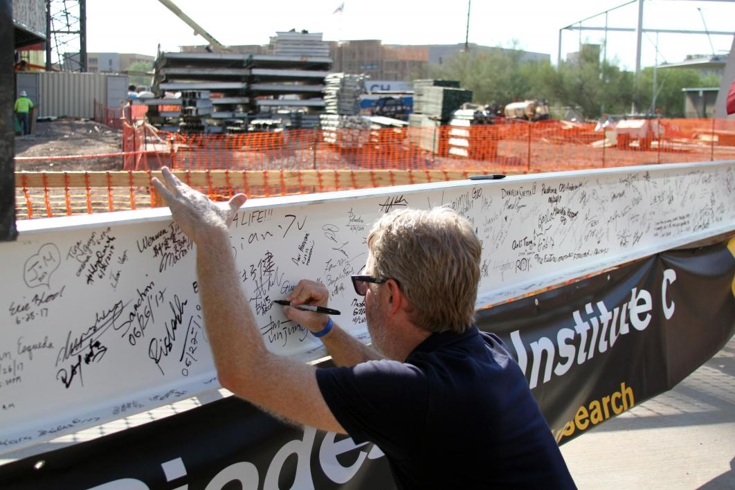 People sign the final beam for Biodesign C