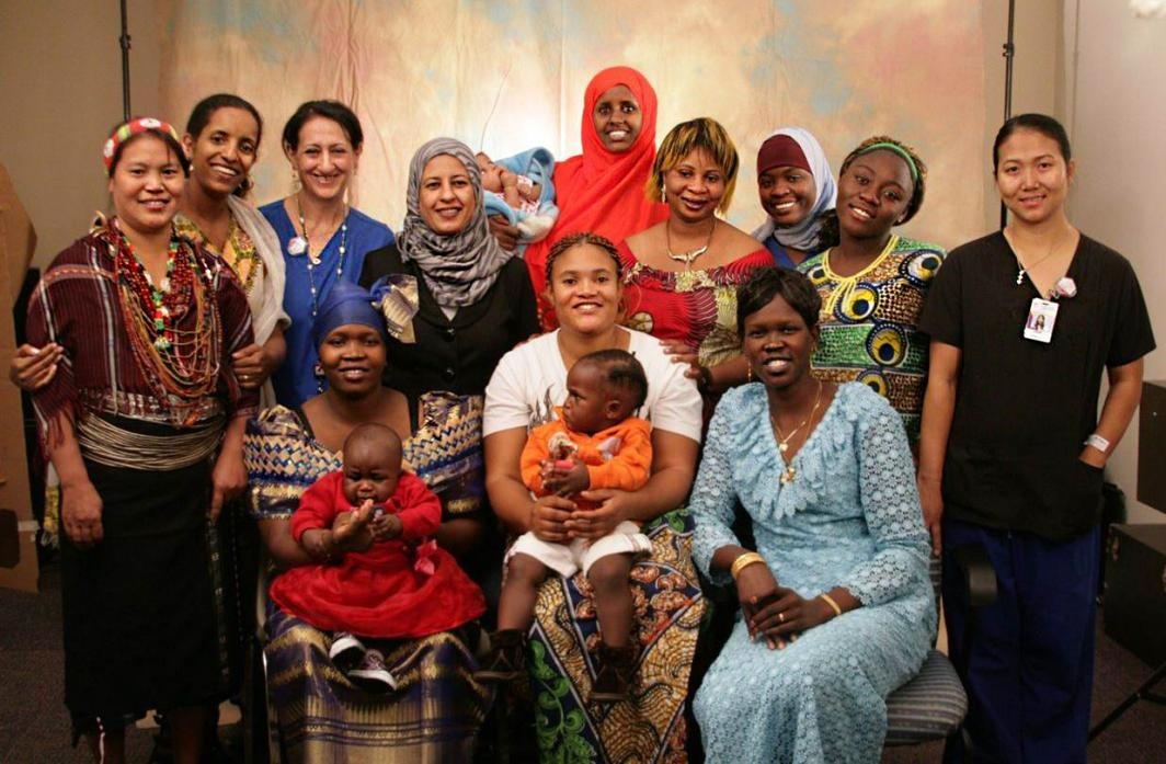 Group of 12 RWHC staff and refugee mothers with 3 babies smiling in front of backdrop
