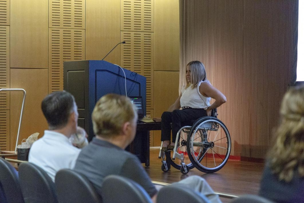 woman in wheelchair on stage speaking to audience