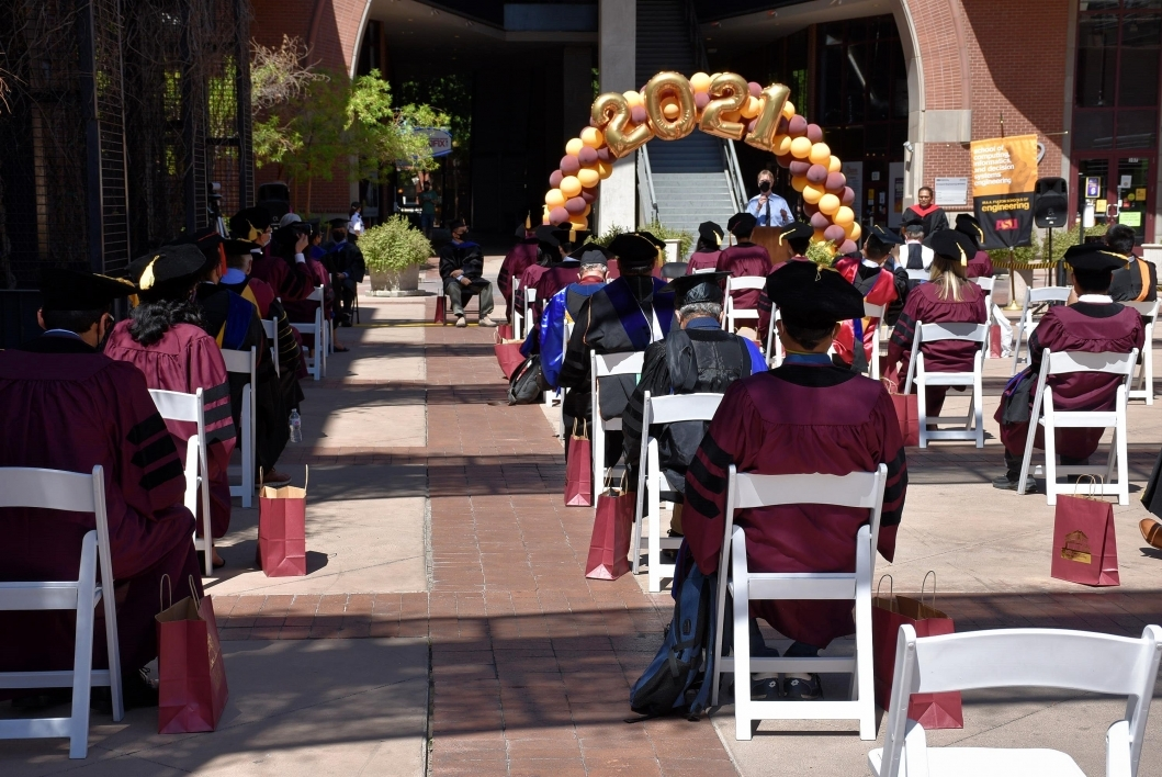 Graduating students sit socially distanced at an outdoor ceremony