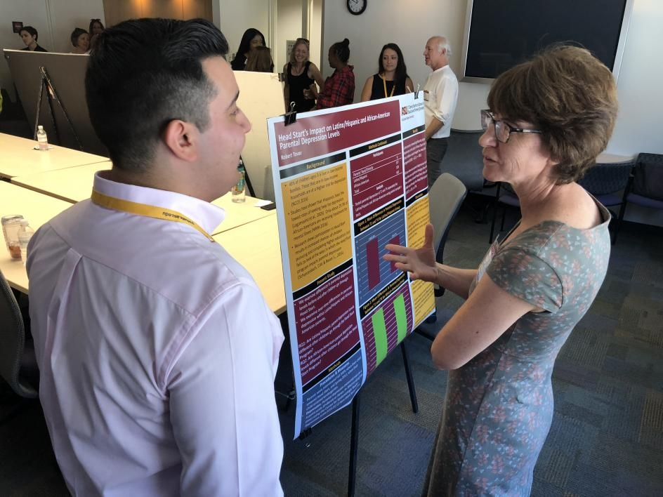 SUPER fellow presenting his research poster to a faculty member.