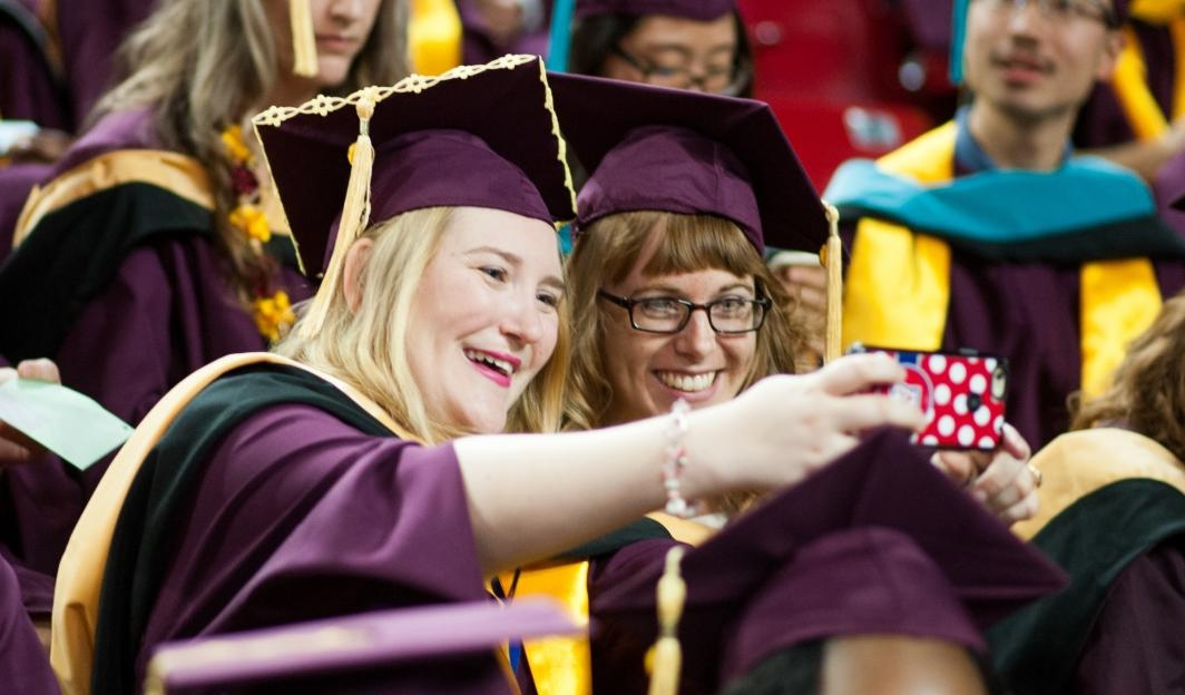 Students take selfies at ASU's Graduate Commencement
