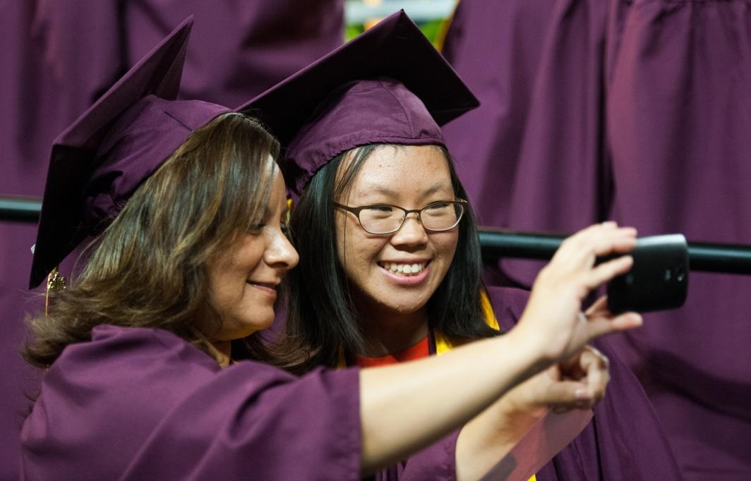 two grads taking a selfie