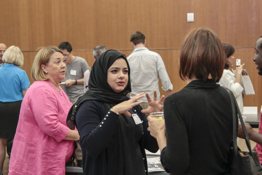 Woman in black hijab gestures in explanation while conversing with another woman during networking.