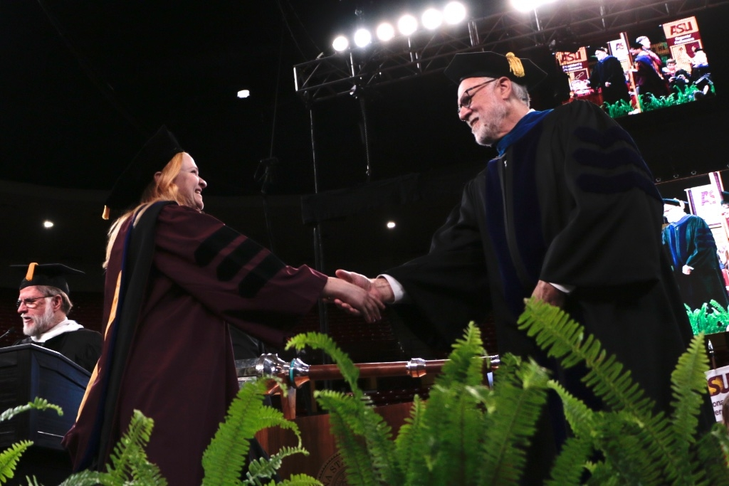 Wendy Caldwell shakes hands with University Provost Mark Searle during ASU Graduate Commencement
