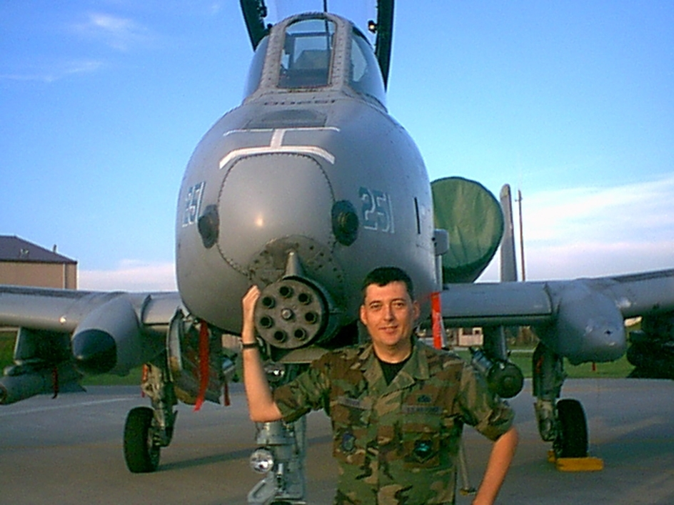 man standing in front of military plane