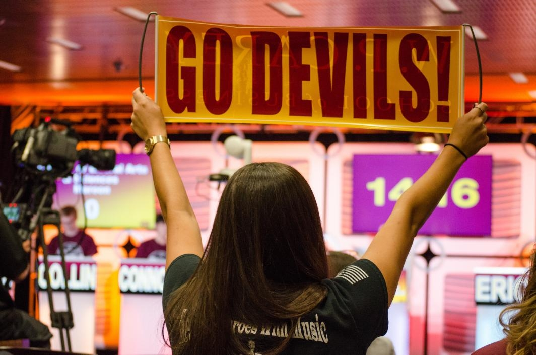 student holding up a Sun Devil banner