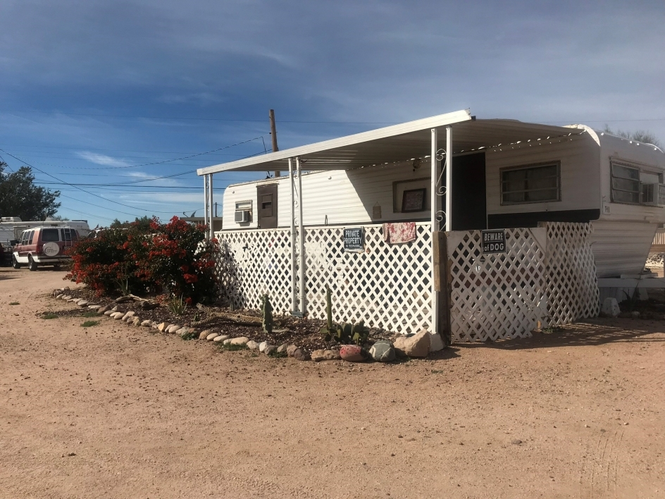 A white mobile home surrounded by a dirt lot and some bushes