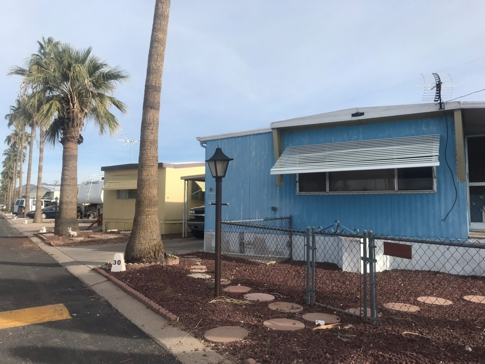 Street lined with mobile homes and palm trees