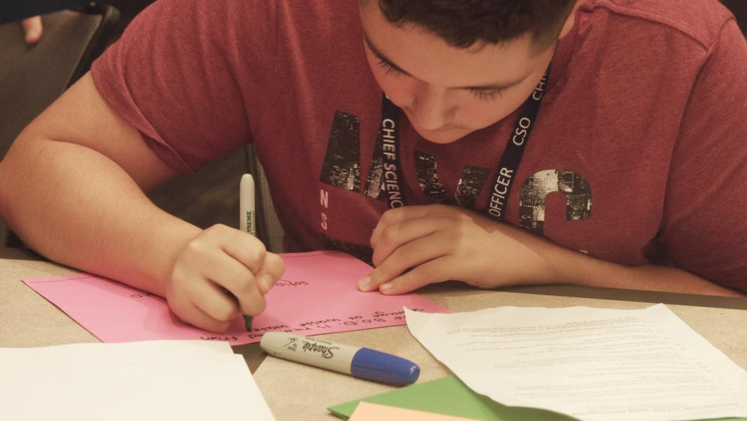 "A student Chief Science Officer writes the caption for a page in his ""Flip Book"" YouTube video."