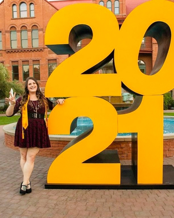 ASU College of Health Solutions graduate Emily Armstrong making the pitchfork sign with her hand as she poses next to a giant 2021 sign