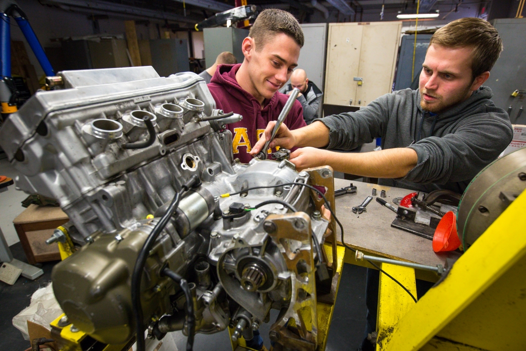Two students work on a car engine.