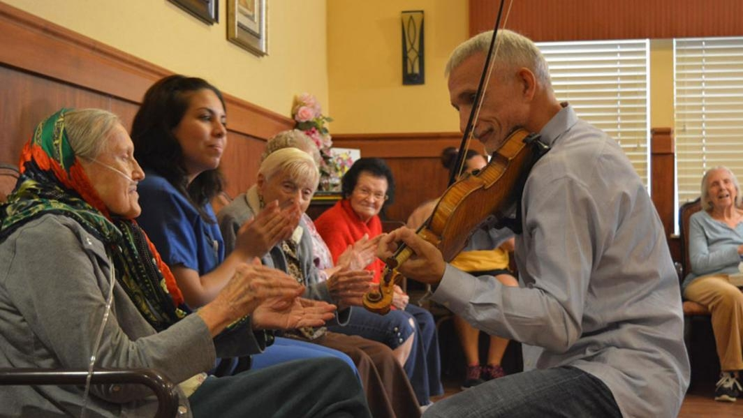 A man plays violin at a nursing home