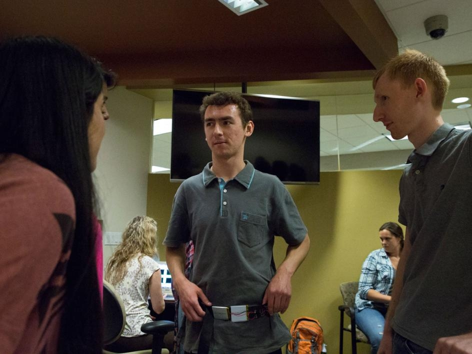 Civil, environmental and sustainable engineering graduate student Jordan Rodriguez (center) tries on the Haptic Compass Belt at the CSE 591: Assistive Technologies Demo session on April 26, 2016.