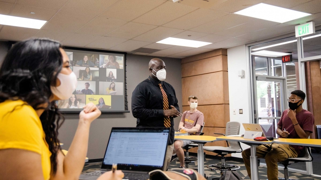 A professor in a mask speaks in front of a classroom of distanced, masked college students