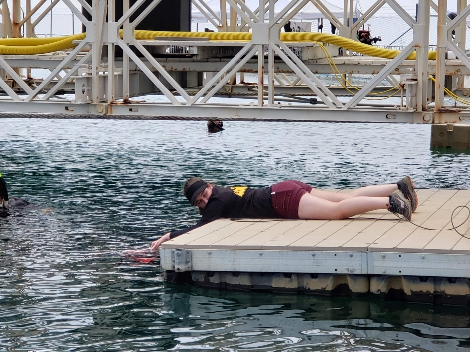 An ASU student lies down on a dock to deploy an autonomous vehicle in water