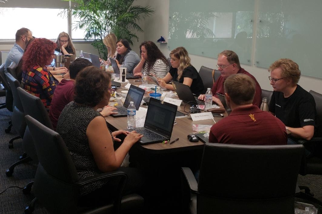 People working on laptops around a conference table