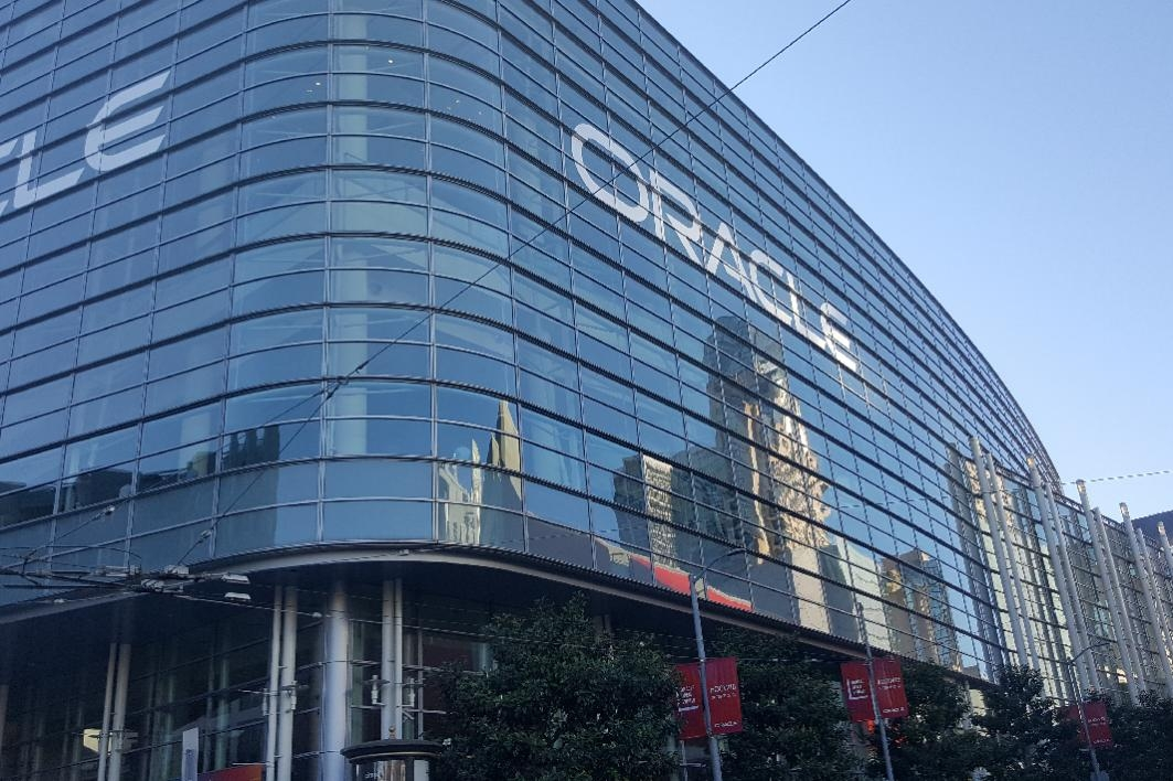 """Glass building with a reflection of San Francisco and """"Oracle"""" projected across the glass windows."""