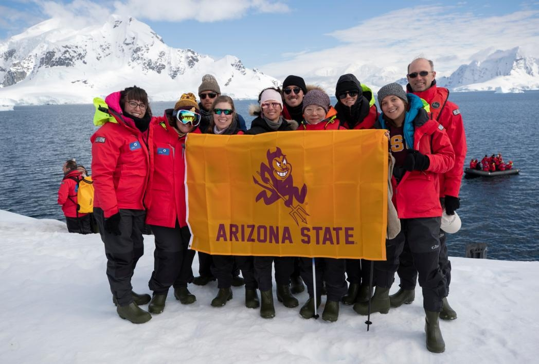 Group of ASU students holding an ASU flag on an iceberg in Antarctica