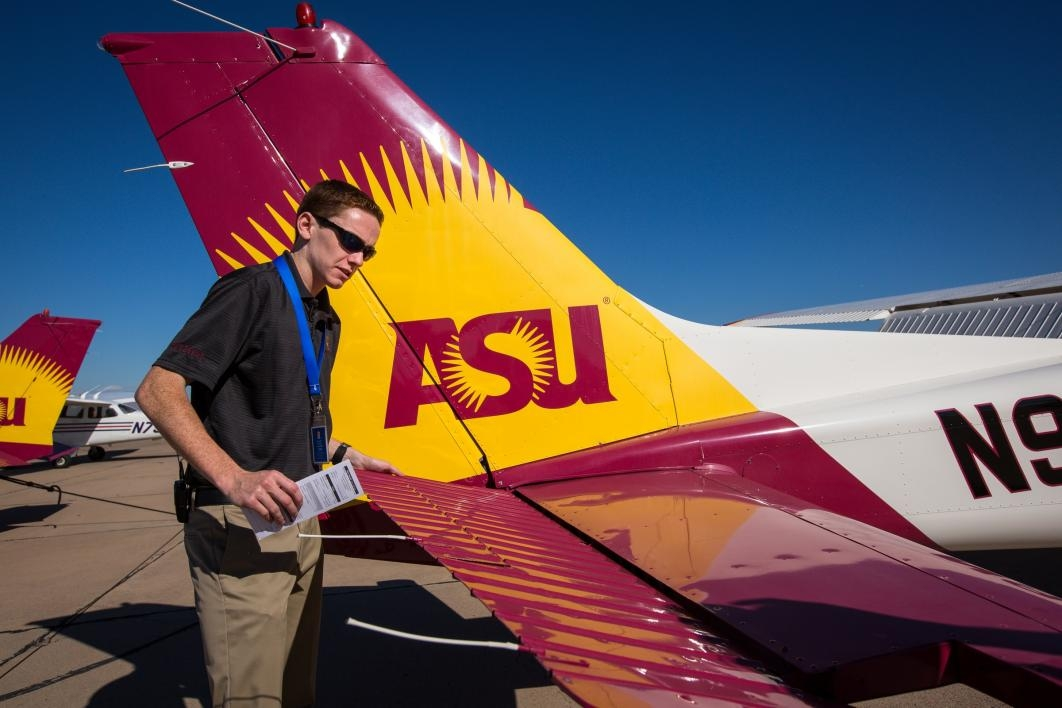 An aviation student checks the plane before takeoff.