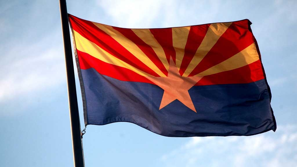 The Arizona state flag on a flagpole and backlit by the sun
