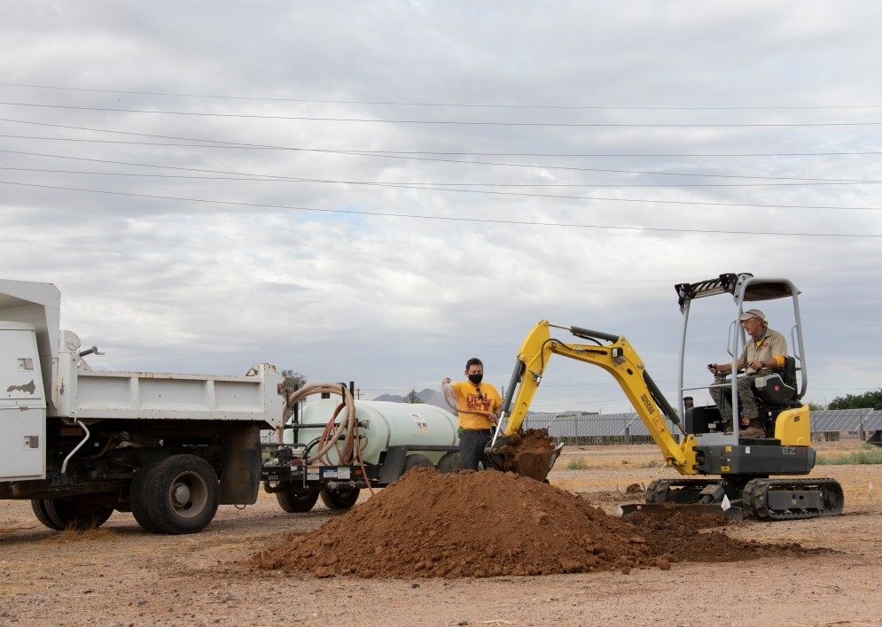 ASU Facilities Management team digging with backhoe and hosing water on dirt to diminish dust