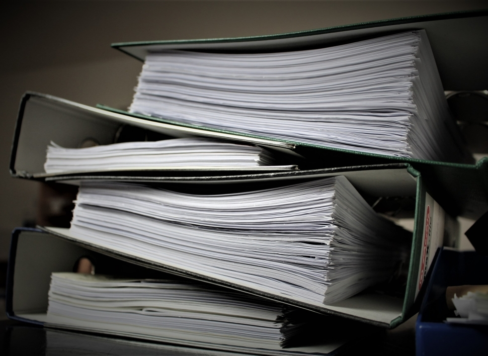 stacks of binders filled with paper