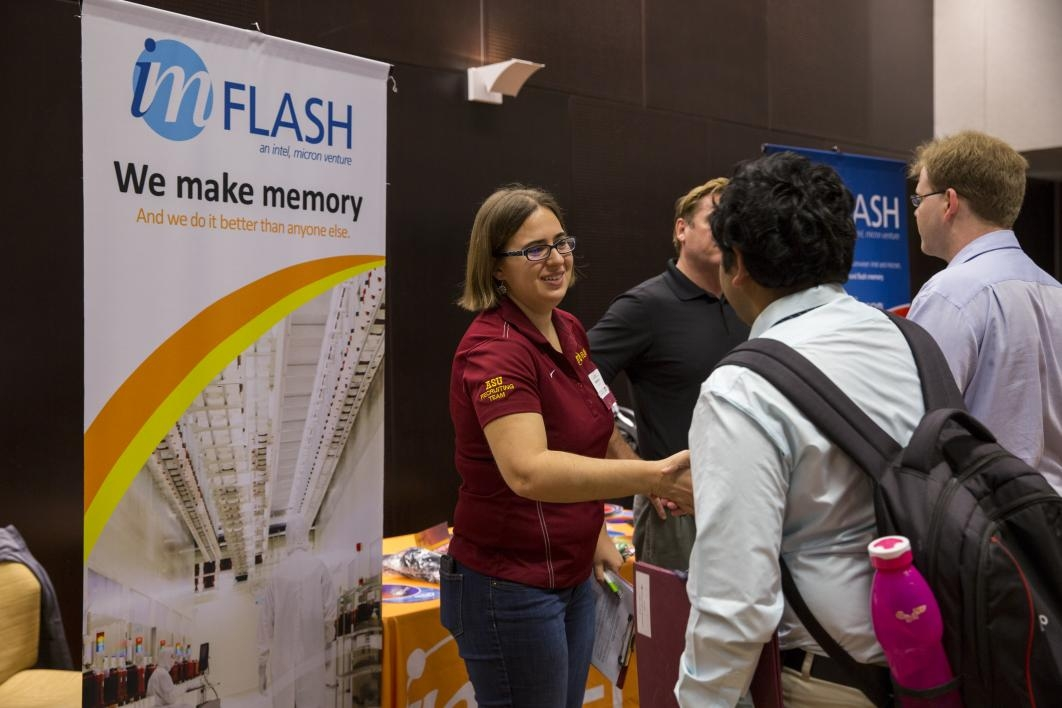 woman shaking hands with student at career fair