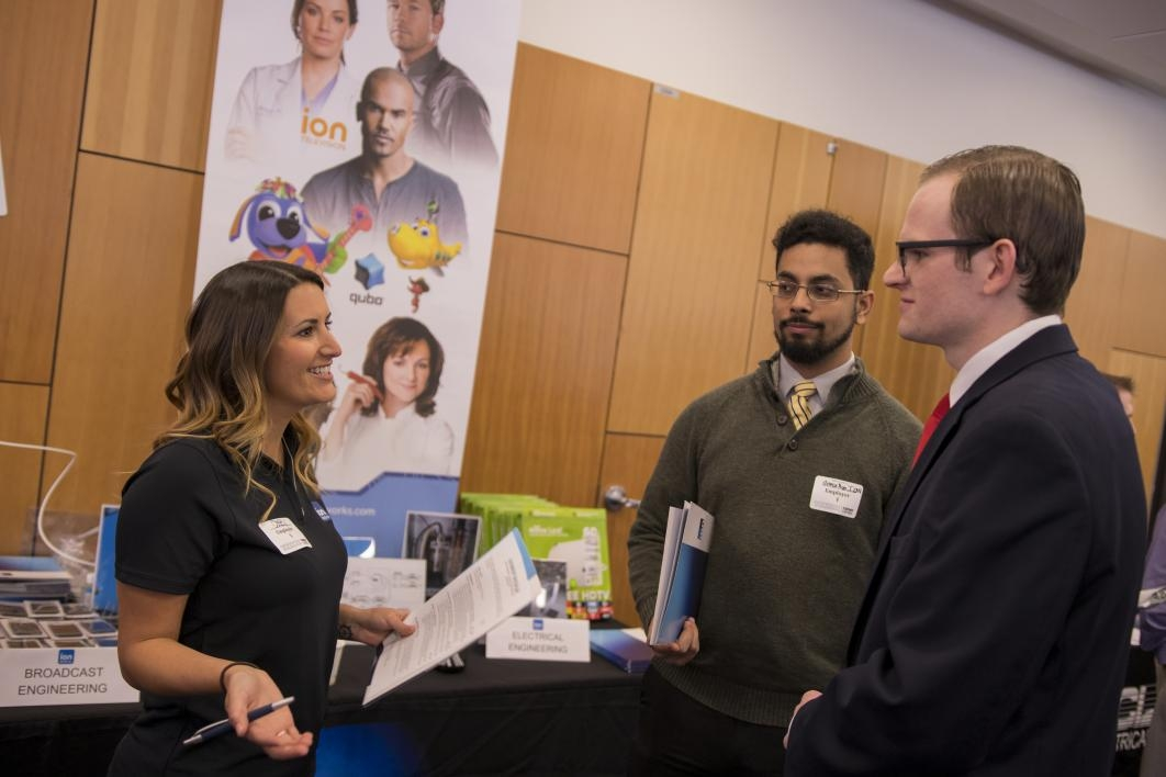 woman talking to two students at career fair