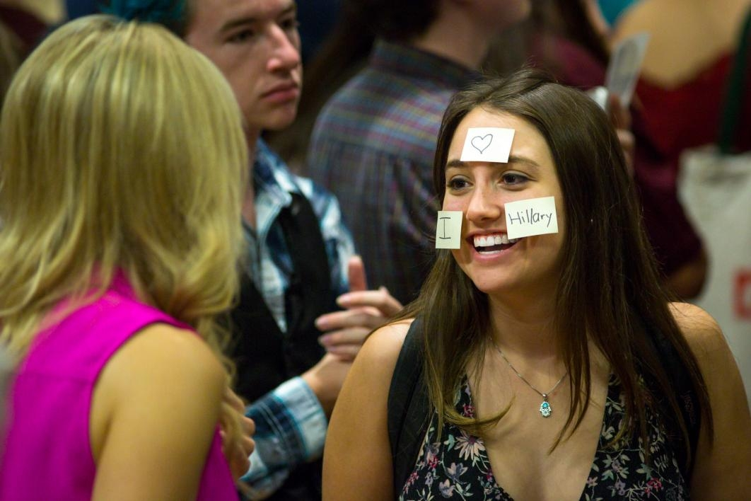 A young woman poses with post-its on her face at the Chelsea Clinton talk