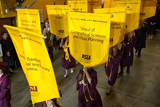 grads carrying banners into convocation