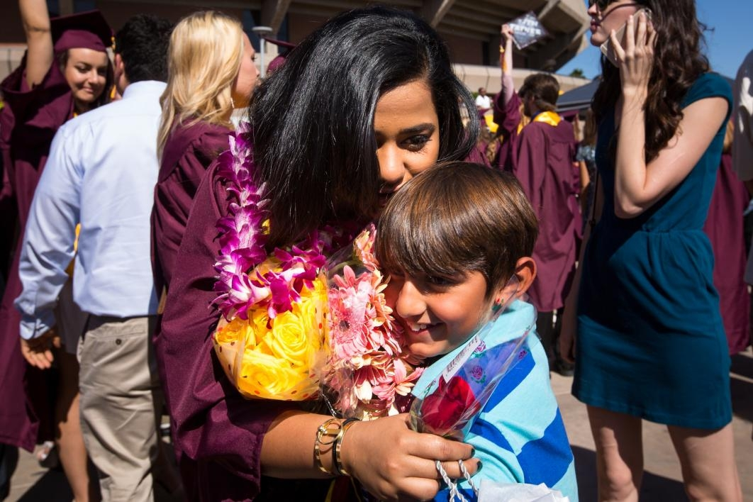 graduate hugging little boy