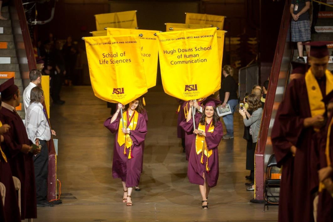graduates carrying school gonfalons