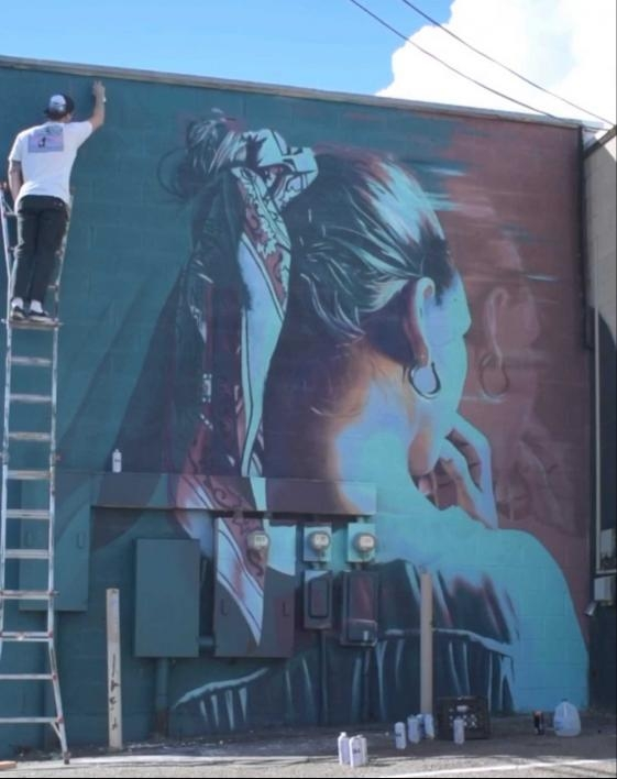 ASU alum and muralist Clyde Thompson paints a mural from a ladder